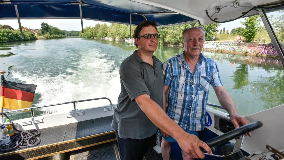 Machen 'ne Welle: Kapitän Heiko Ebkes (r.) schippert mit Fahrschüler Ben über den Stichkanal in Limmer, passt auf, dass der Neu-Skipper auf Kurs bleibtFoto: HENNING SCHEFFEN PHOTOGRAPHY